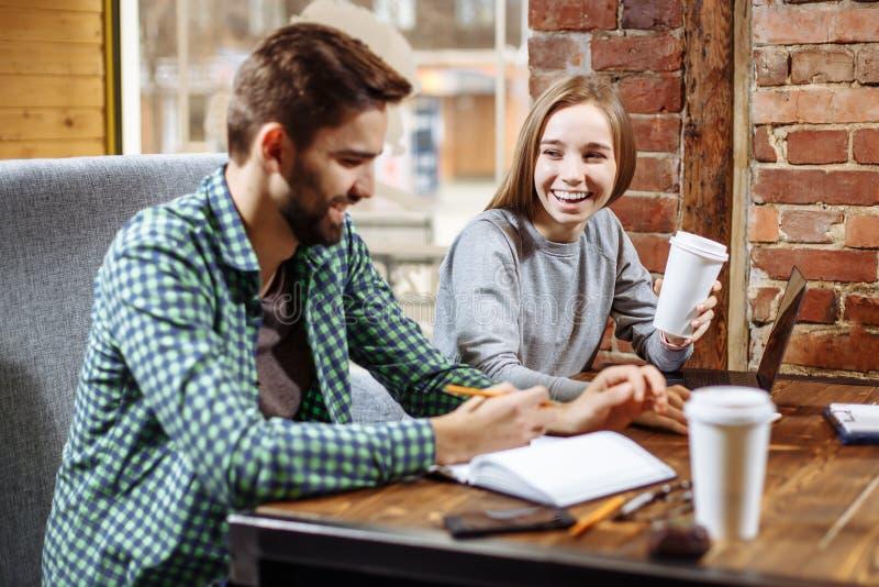 Jong houdend van paar, studenten, die in een koffie zitten terwijl het leren samen en het voorbereidingen treffen voor het semina royalty-vrije stock afbeeldingen