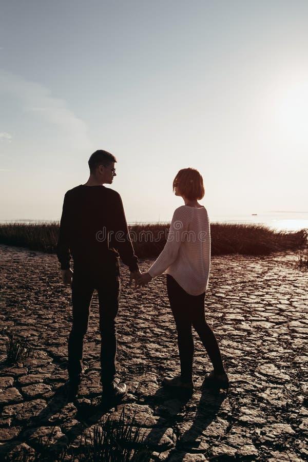 Jong houdend van paar van tieners in zonnebril die handen houden stock foto's