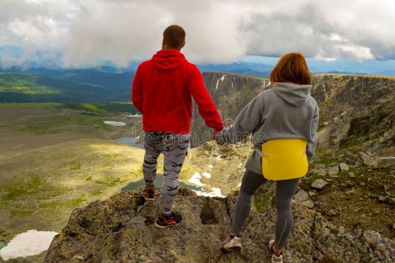 Jong houdend van paar van toeristen handen houden die zich bevindt bovenop royalty-vrije stock afbeeldingen