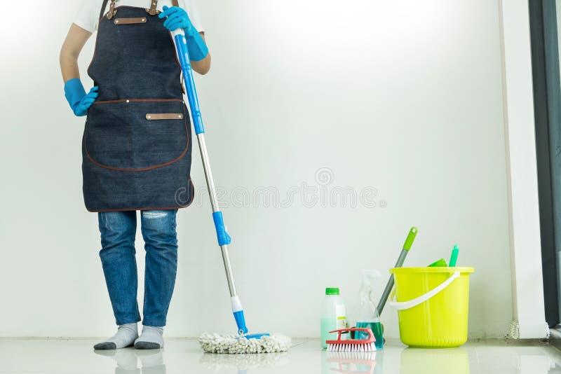 Jong huishoudster het schoonmaken vloer het mobbing holdingszwabber en plastiek stock afbeelding