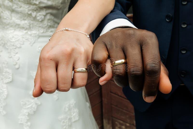 Jong huwelijkspaar dat hun ringen toont sigh die op witte achtergrond wordt ge?soleerdo royalty-vrije stock fotografie