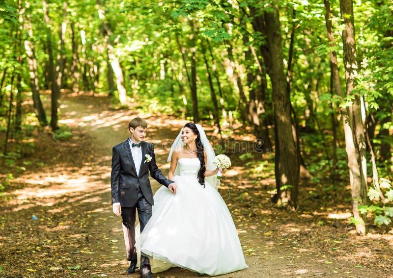 Jong huwelijkspaar die in openlucht lopen stock foto's