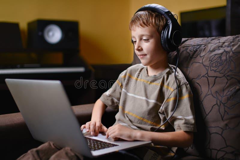 Jong jong geitje die aan muziek luisteren en Internet doorbladeren stock afbeelding