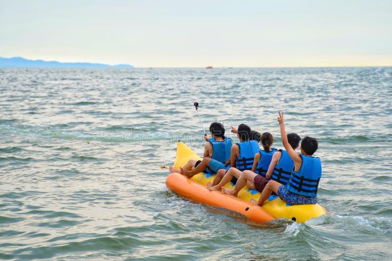 Jong jongens en meisje die op de banaanboot berijden op het overzees in Pattaya, Thailand stock afbeeldingen