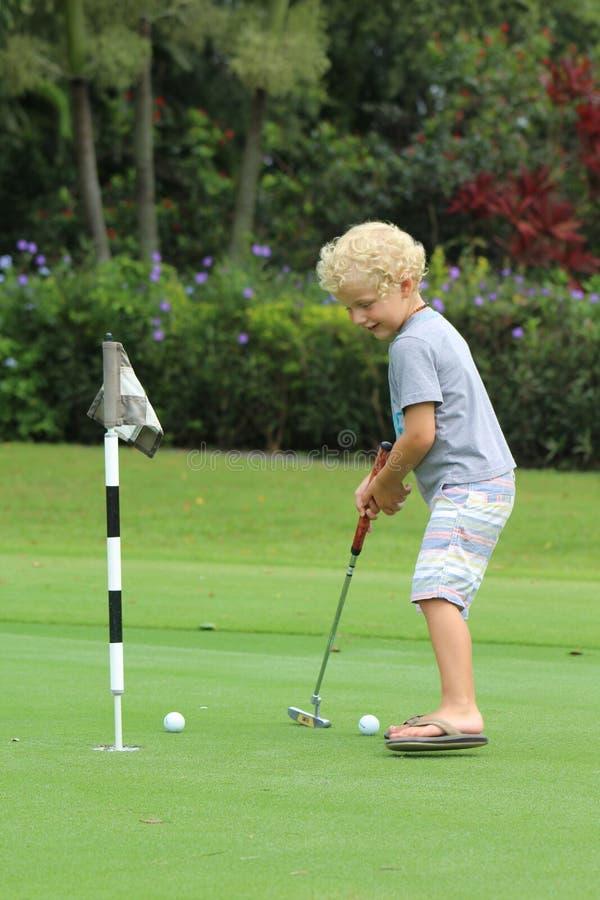 Jong jongens speelgolf royalty-vrije stock afbeelding