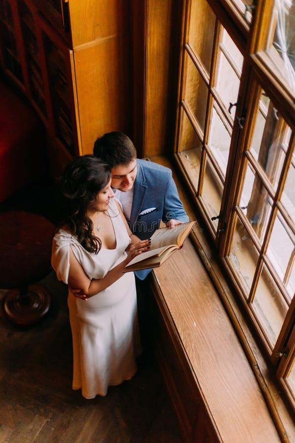 Jong jonggehuwdepaar die in bibliotheek dichtbij venster omhelzen De charmante bruid leunt aan haar knappe bruidegom, die boek ho royalty-vrije stock foto's