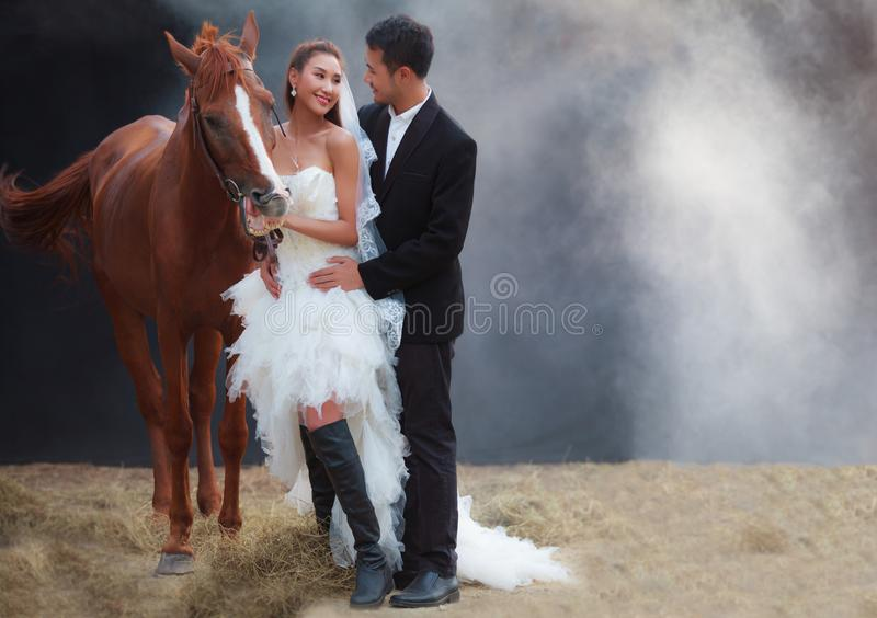 Jong jonggehuwdepaar, mooie schoonheidsbruid in kostuum van het manier het witte bruids huwelijk en knappe bruidegom die door spi stock foto