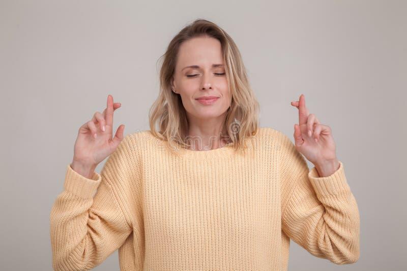Jong Kaukasisch blondewijfje die haar ogen sluiten die vingers met hoop kruisen, die belangrijk nieuws voorzien het dragen van ge stock afbeelding