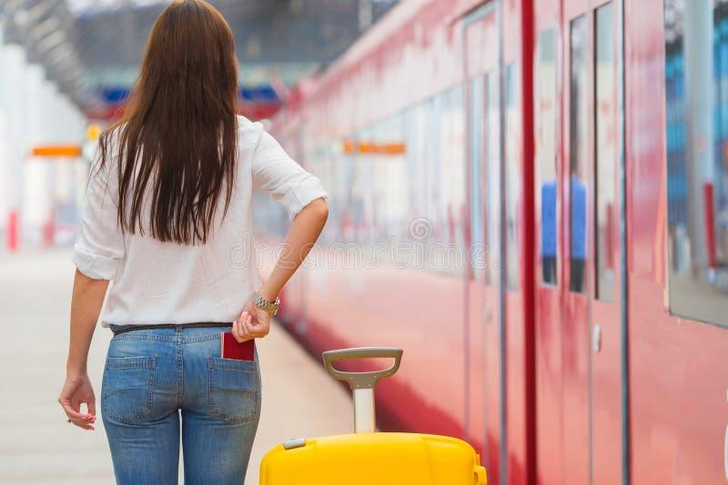 Jong Kaukasisch meisje met bagage bij post die door trein reizen stock foto's