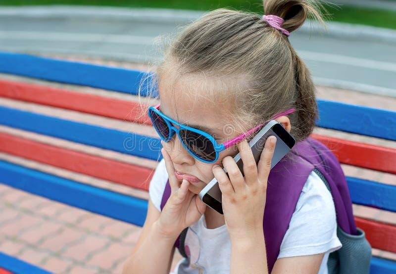 Jong Kaukasisch meisje met een droevig gezicht die mobiele telefoon houden, telefonerend, sprekend op de telefoon, die op bank bi stock foto