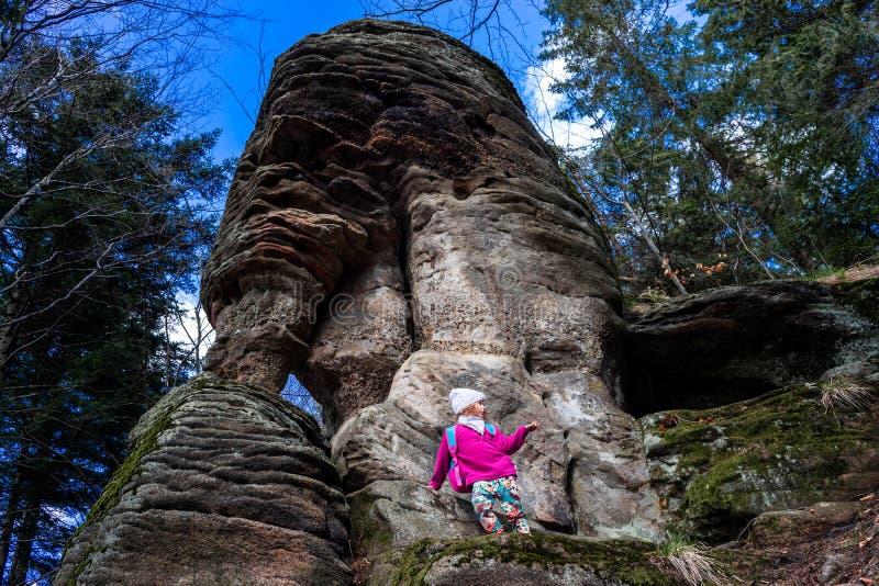 Jong Kaukasisch meisje onder rotsen in een bos en bomen stock afbeeldingen