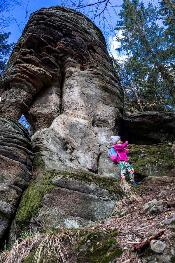 Jong Kaukasisch meisje onder rotsen in een bos en bomen royalty-vrije stock fotografie
