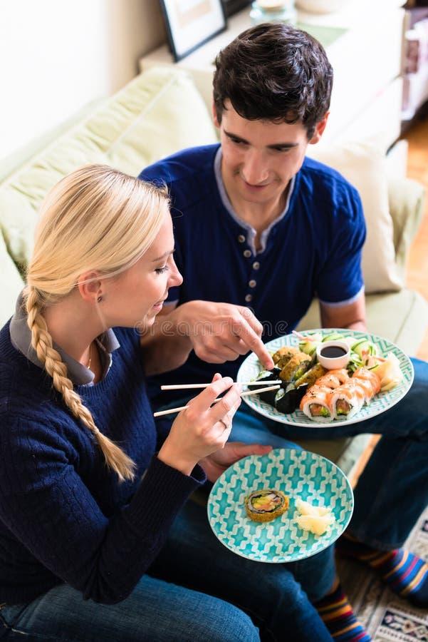 Jong Kaukasisch paar die Aziatisch traditioneel voedsel thuis eten royalty-vrije stock foto's