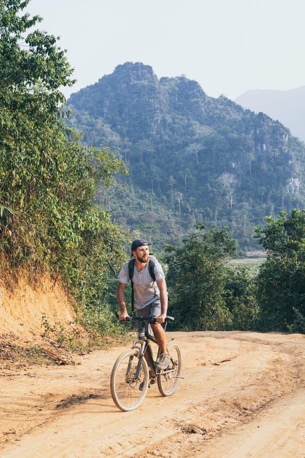 Jong Kaukasisch personenvervoer een bergfiets bergopwaarts in het dorp van Muang Ngoi, Laos royalty-vrije stock foto