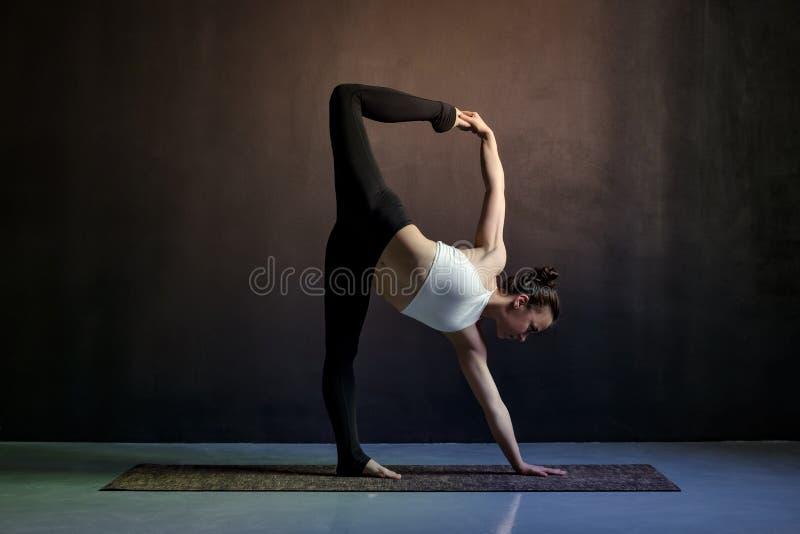 Jong Kaukasisch slank yogameisje die variatie van shvanasana van adhomukha doen royalty-vrije stock afbeelding