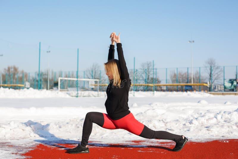 Jong Kaukasisch vrouwelijk blonde in violette beenkappen die oefening op een rode renbaan in een sneeuwstadion uitrekken pasvorm  royalty-vrije stock afbeelding