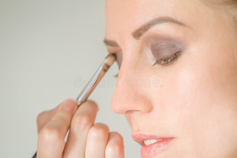Jong Kaukasisch vrouwelijk model bij een make-up Het van toepassing zijn maakt tot a royalty-vrije stock foto's
