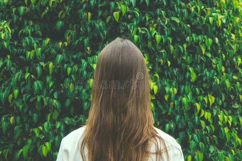 Jong Kaukasisch Vrouwenmeisje met Lang Kastanjehaar die zich met terug naar Kijker op Groen Forest Tree Foliage Background bevind royalty-vrije stock afbeelding