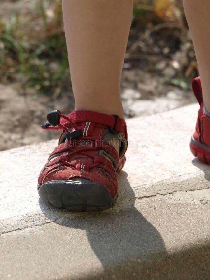 Jong kind die naar de camera in moderne rode schoenen lopen royalty-vrije stock foto's