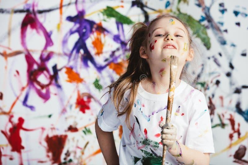 Jong kindschilder die zich met een borstel bevinden stock foto