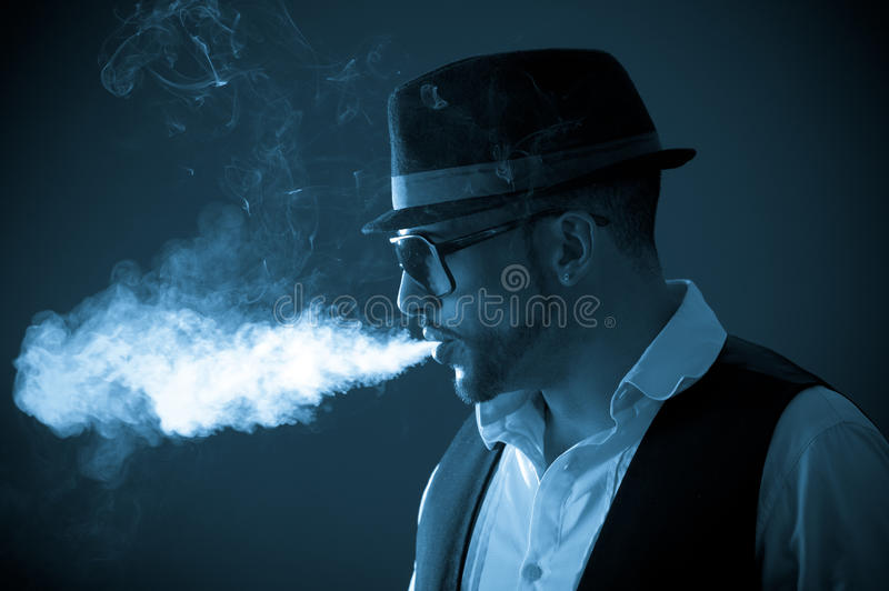 Jong knap modieus mannelijk model die a roken stock fotografie