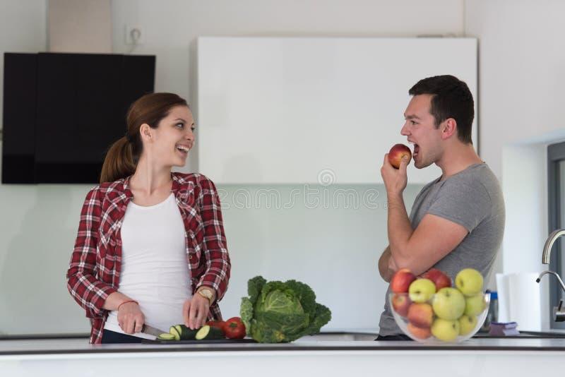 Jong knap paar in de keuken stock afbeelding