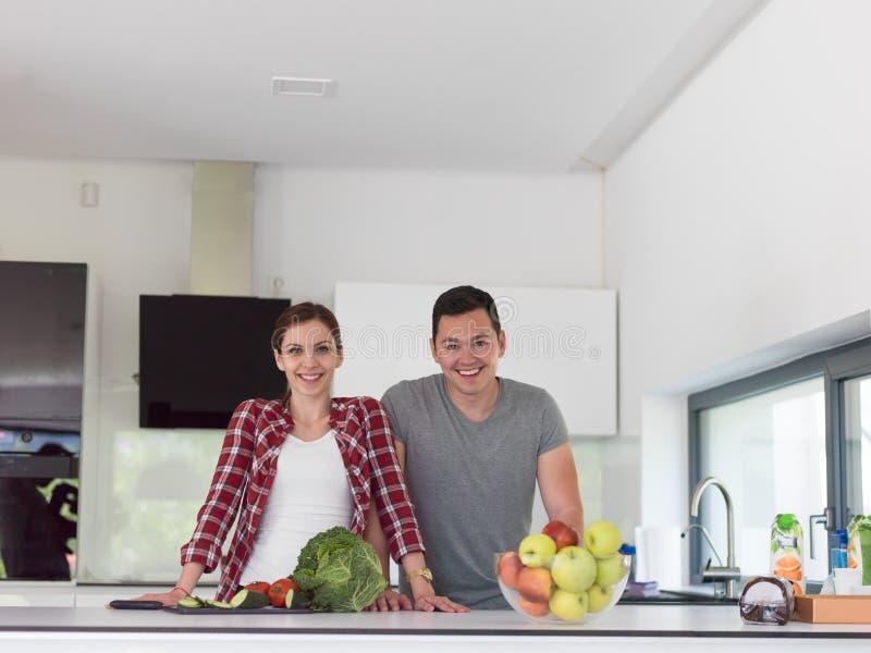 Jong knap paar in de keuken stock foto