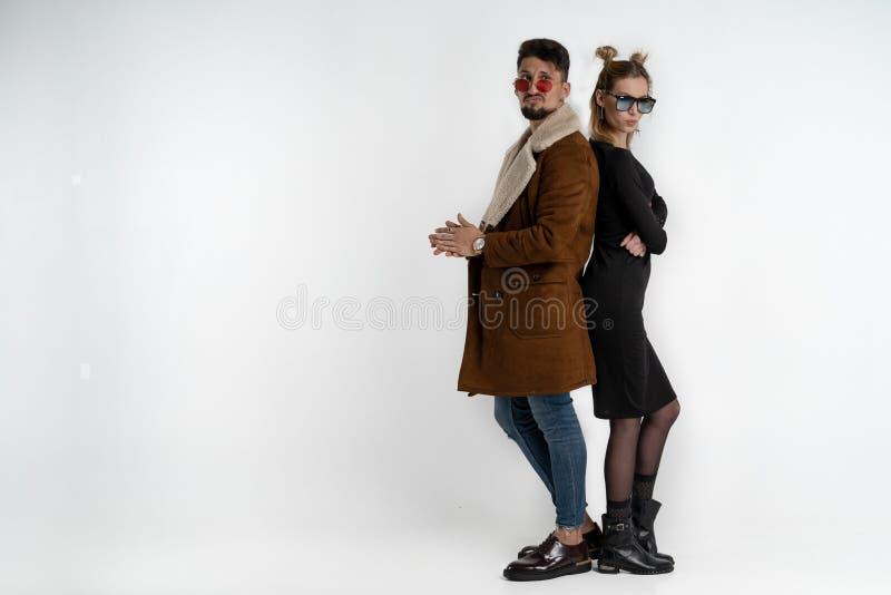 Jong knap paar in modieuze in vrijetijdskleding die het rijtjes bekijken de over ge?soleerde camera bevinden zich royalty-vrije stock afbeeldingen