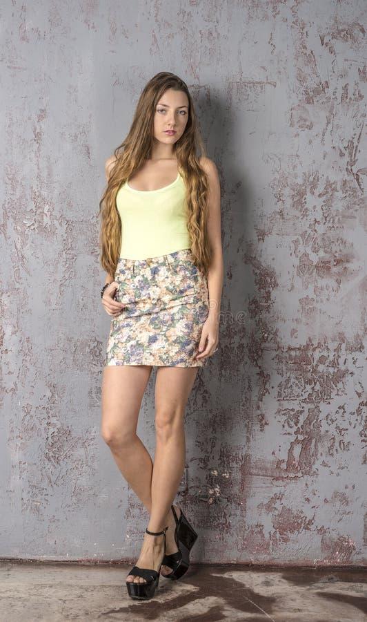 Jong langharig mager meisje met lange benen in een hoogste minirok en platformsandals stock afbeelding