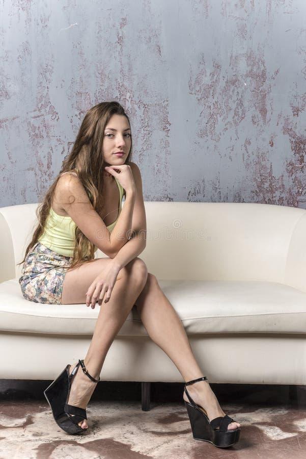 Jong langharig mager meisje met lange benen in een hoogste minirok en platformsandals stock foto's