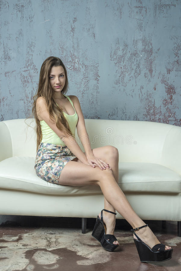 Jong langharig mager meisje met lange benen in een hoogste minirok en platformsandals stock fotografie