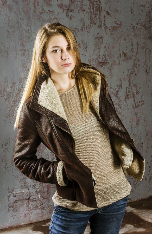 Jong langharig meisje in een leerjasje met bontkraag en jeans royalty-vrije stock afbeeldingen
