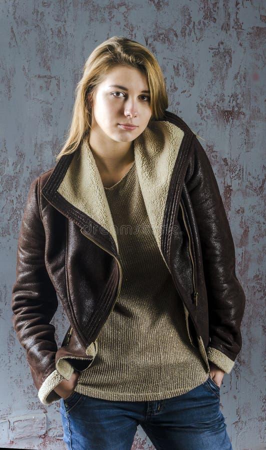 Jong langharig meisje in een leerjasje met bontkraag en jeans royalty-vrije stock fotografie