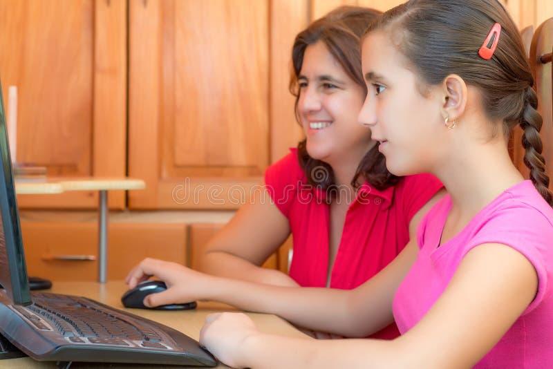 Jong Latijns meisje en haar moeder die aan een computer werken stock afbeelding