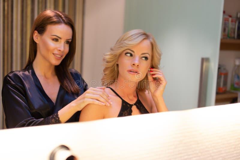 Jong lesbisch paar die in badkamers zich in spiegel kleden royalty-vrije stock fotografie