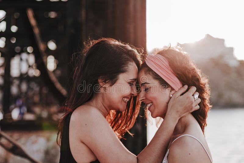 Jong lesbisch paar die bij zonsondergang in openlucht koesteren Levensstijl en trotsconcept De liefde is liefde stock fotografie