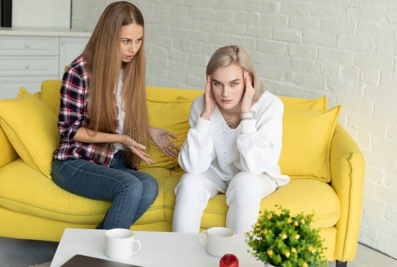 Jong lesbisch paar die in ruzie, vrijetijdskleding dragen, die op gele bank thuis zitten stock afbeelding