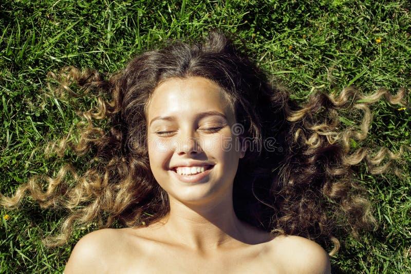 Jong leuk de zomermeisje op gras buiten het ontspannen royalty-vrije stock foto's
