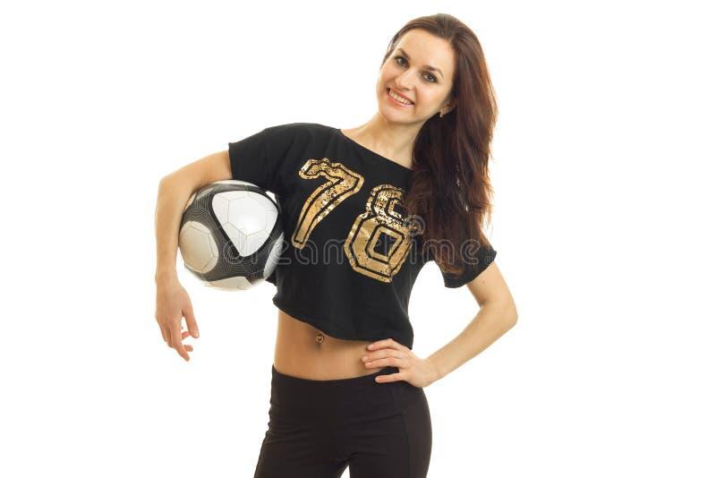 Jong leuk donkerbruin meisje die met voetbalbal in haar handen op camera glimlachen stock foto