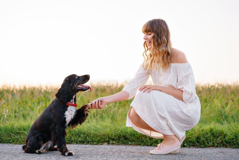 Jong leuk meisje die een hond Russisch Spaniel opleiden Zwarte doggie geeft zijn poot aan haar maitresse Zonsondergang in aard royalty-vrije stock foto's