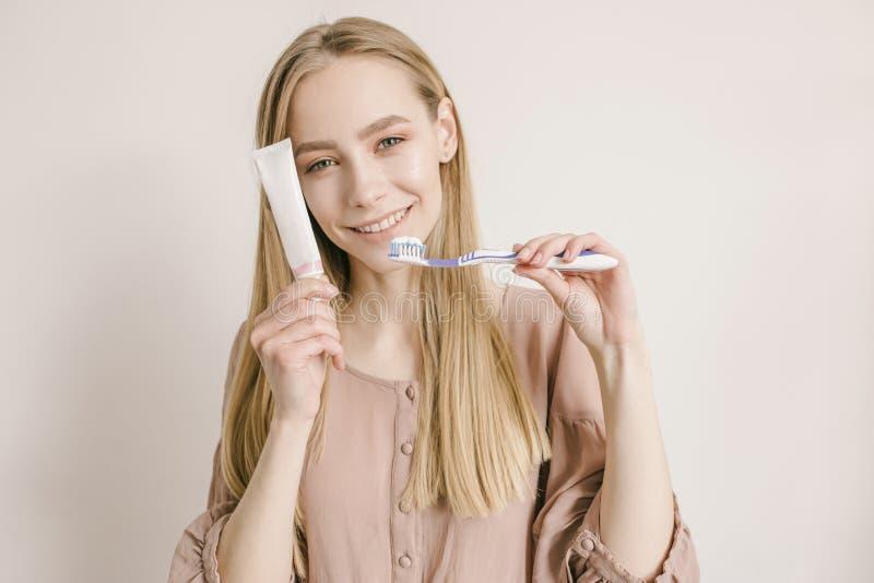 Jong leuk meisje met wit deeg en tandenborstel in haar handensi die en camera smilling onderzoeken Witte achtergrond stock foto