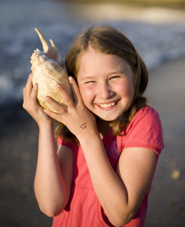 Jong leuk meisje met zeeschelp bij zeekust het glimlachen royalty-vrije stock afbeeldingen
