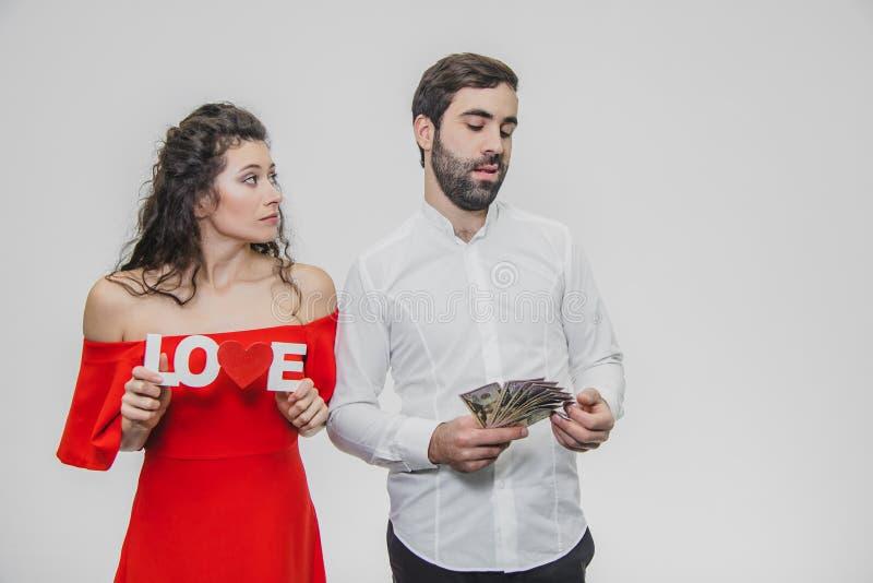 Jong leuk paar in liefde Een man houdt geld in zijn handen, een vrouw met een houten woord van liefde Geïsoleerdn op een wit royalty-vrije stock afbeelding