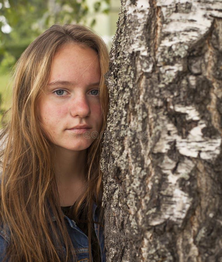 Jong leuk tienermeisje met lang haarportret dichtbij de boom stock afbeeldingen