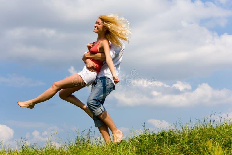 Jong liefdepaar dat pret op de lenteweide heeft royalty-vrije stock foto