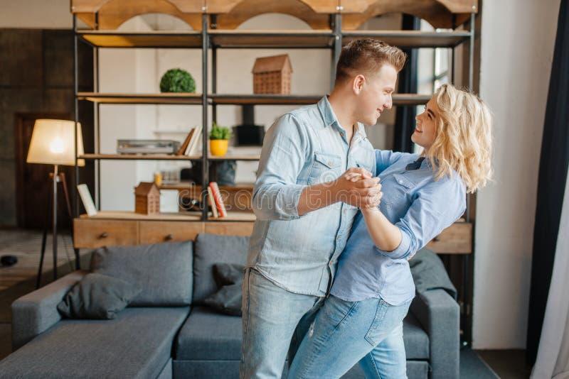 Jong liefdepaar die, romantisch diner thuis dansen royalty-vrije stock foto