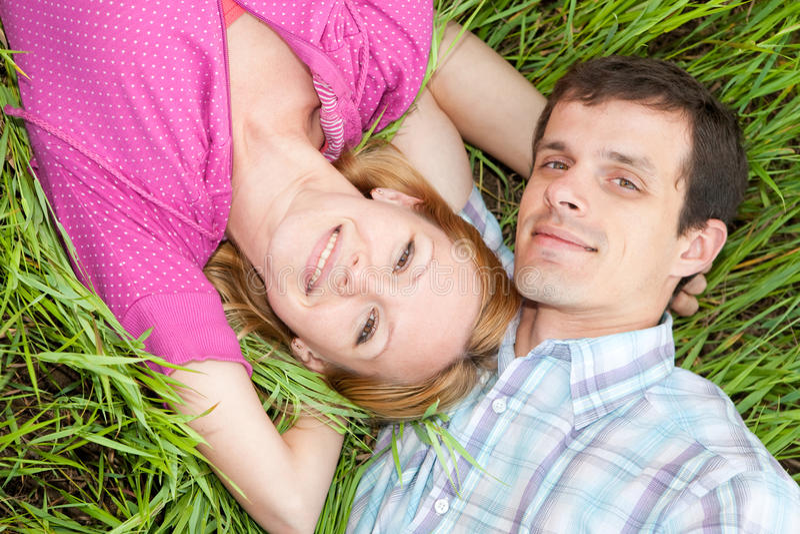 Jong liefdepaar op gras royalty-vrije stock afbeelding