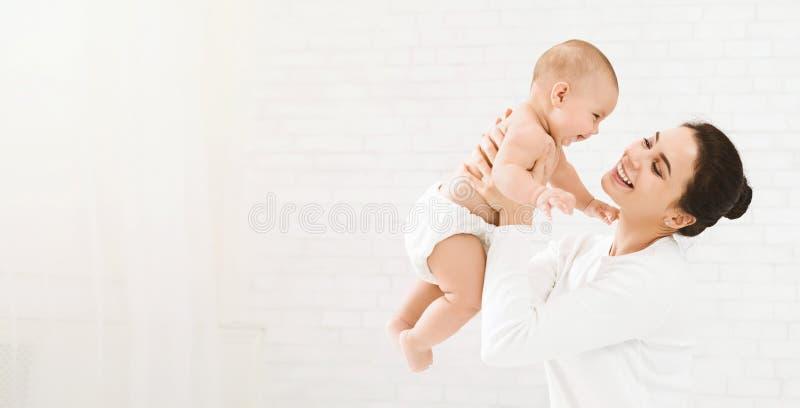 Jong mamma die haar gelukkige baby in lucht houden stock afbeelding