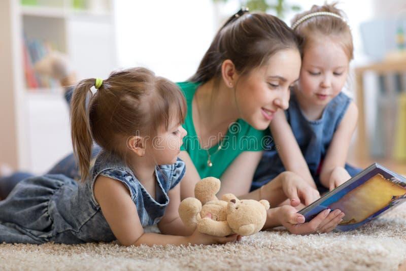 Jong mamma en haar kinderen die op de vloer liggen en boek lezen stock foto's