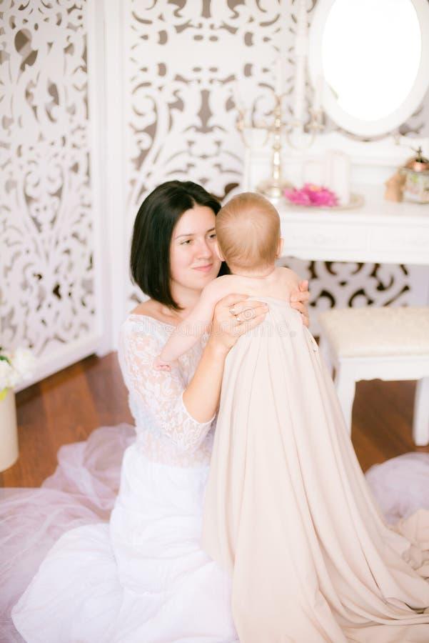 Jong mamma met een baby in haar wapens in de heldere slaapkamer stock foto